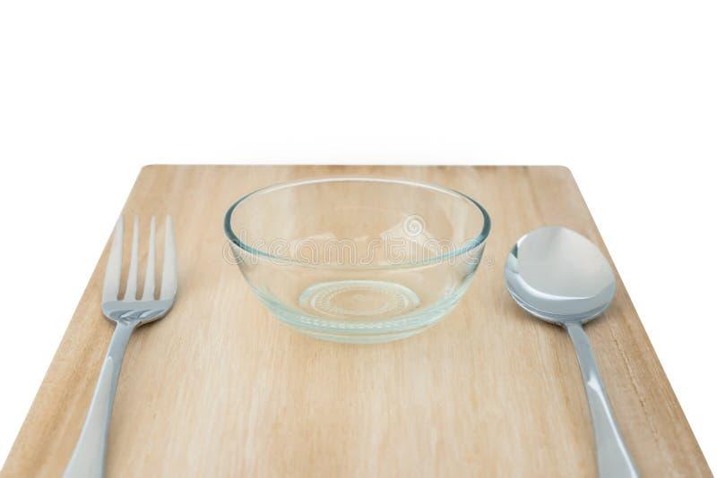 木切板和套叉子和匙子和小碗在白色背景或者沙拉的隔绝的食物、谷物 库存照片