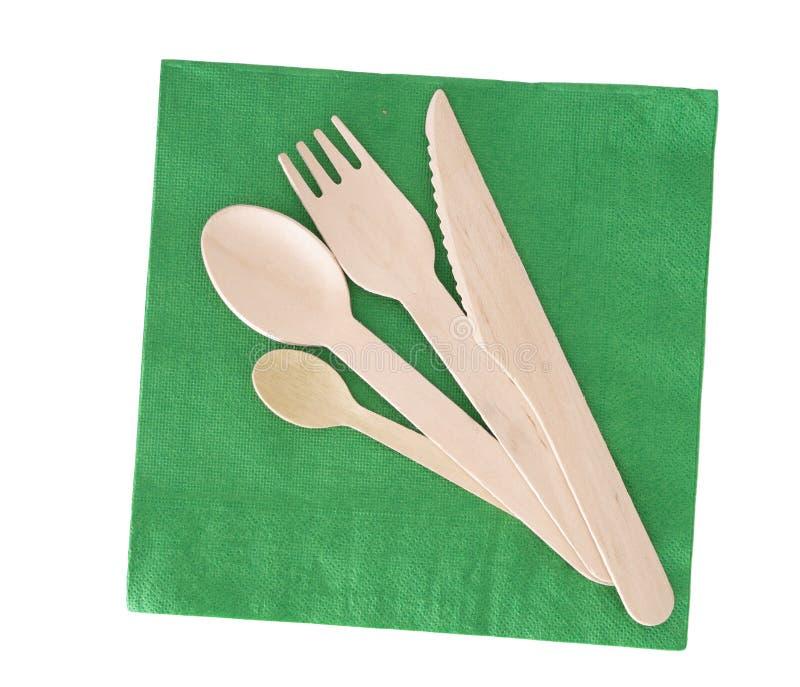 木利器,叉子,匙子,有在白色隔绝的绿皮书餐巾的刀子 免版税库存照片