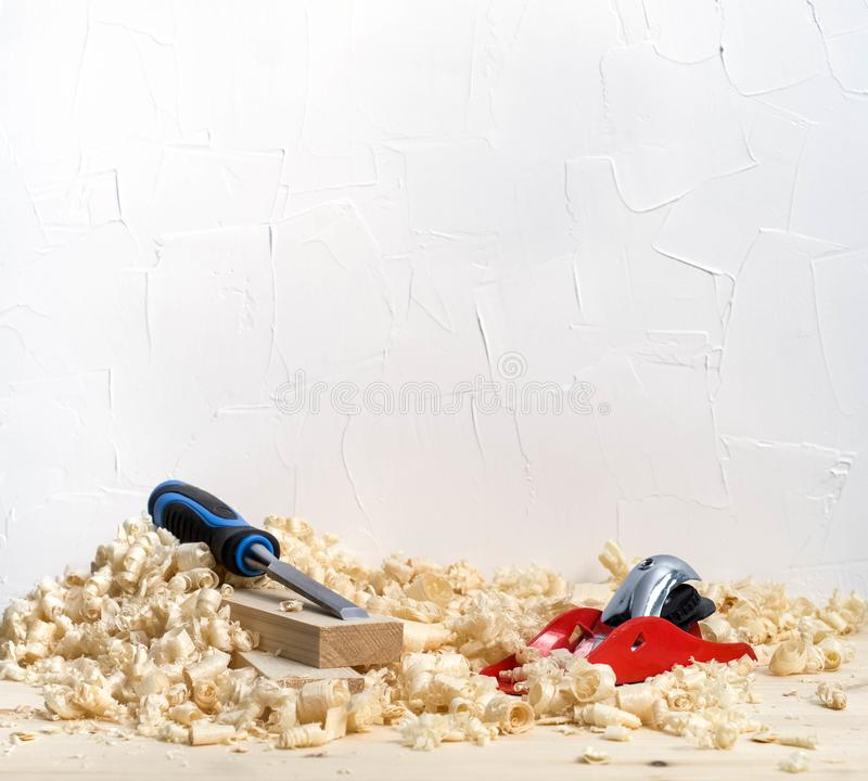 木制品:小红色飞机和凿子在委员会削片的 库存照片