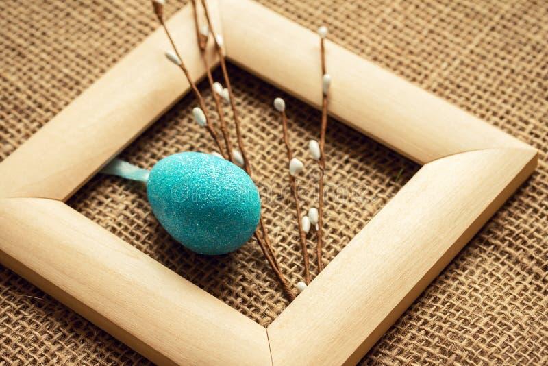 木制框架、复活节彩蛋和杨柳在麻袋布分支 库存照片