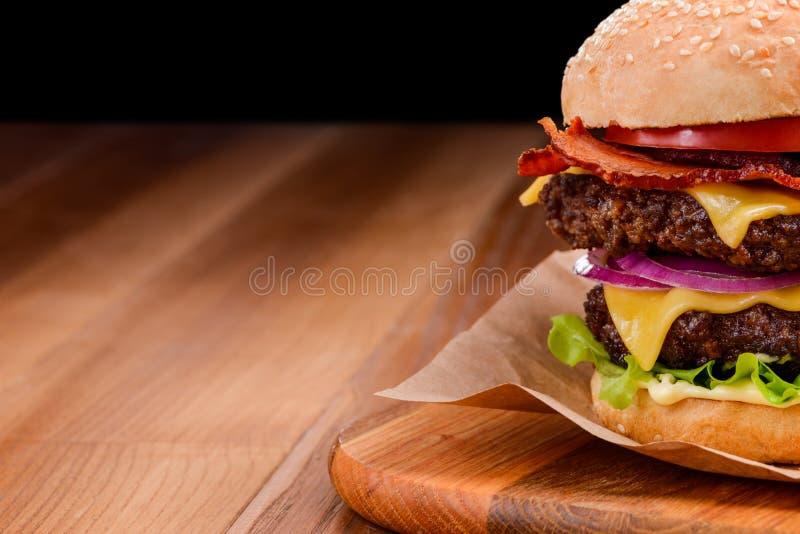 木制背景中双份奶酪汉堡的特写 免版税库存图片