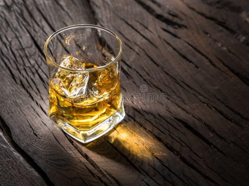 木制背景中的威士忌玻璃或冰块的威士忌酒杯 免版税库存照片