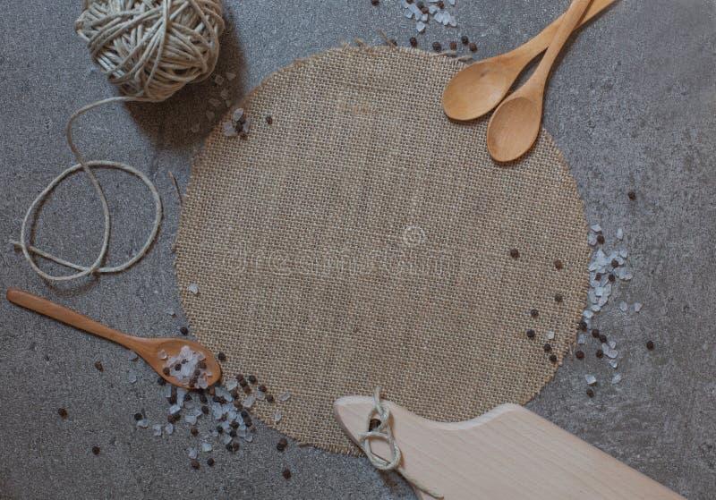 木匙子、切板和线团在石背景 库存图片