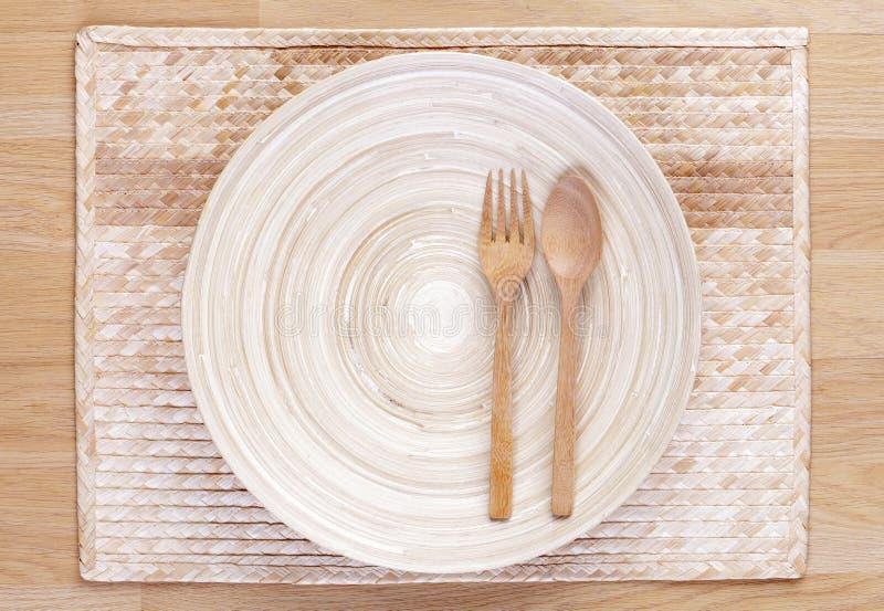 木匙子和叉子和倒空木盘 免版税库存图片