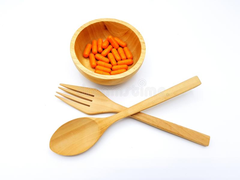 木匙子和叉子横渡与在白色背景隔绝的木碗的橙色草本胶囊 免版税库存照片