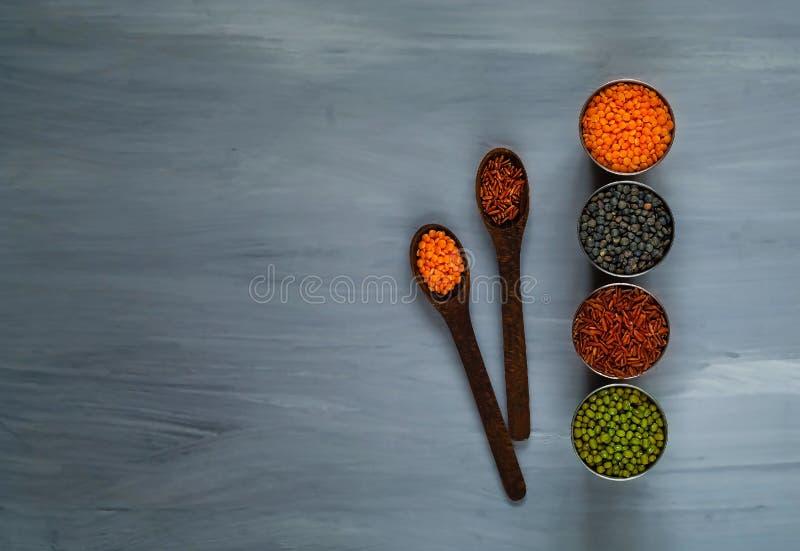 木匙子和各种各样的谷物在金属杯子,健康吃的概念 顶视图 土气白色背景 库存照片