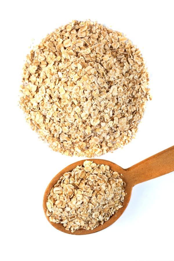 木匙子在白色背景的燕麦片剥落,名列前茅vi 免版税库存照片