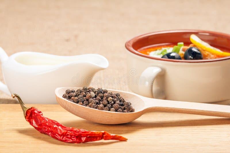 木匙子用黑干胡椒、干红辣椒在切板和陶瓷汤碗有藜科冈羊栖菜属植物和调味汁瓶的 库存图片