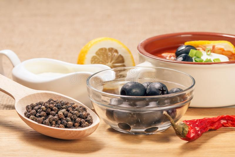 木匙子用黑干胡椒、碗用橄榄,干红辣椒在切板和陶瓷汤碗有藜科冈羊栖菜属植物的, 免版税库存照片