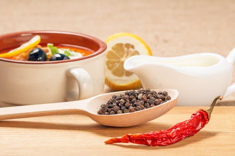 木匙子用黑干胡椒,在切口的干红辣椒 免版税库存图片