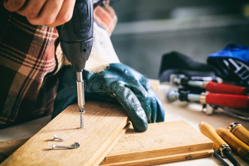 木匠与一把电螺丝刀一起使用 库存照片
