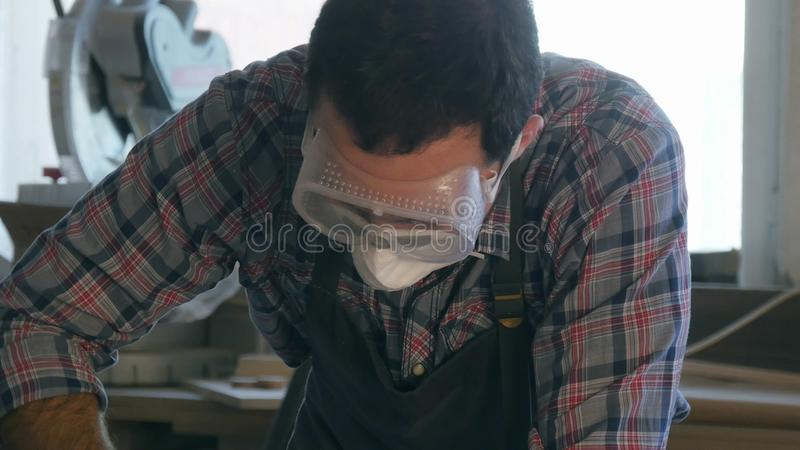 木匠与在木工厂佩带的安全玻璃的工业工具一起使用 免版税库存照片