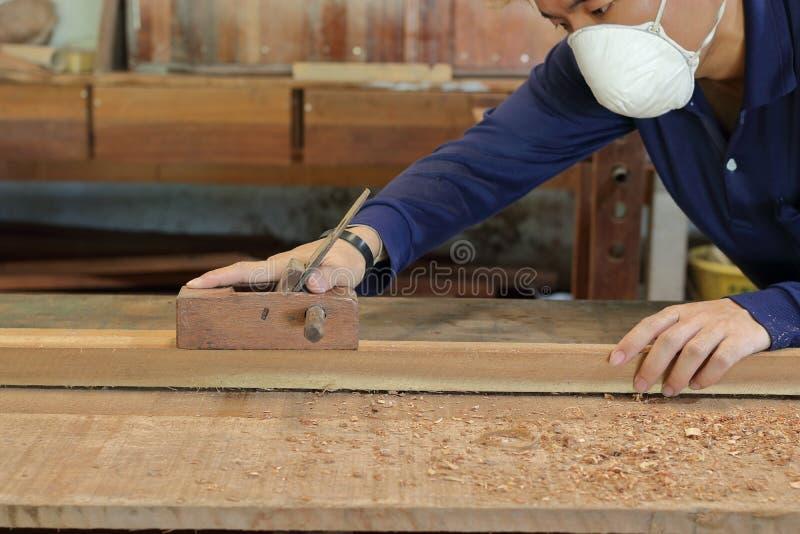 木匠与在木头板条的一台手整平机一起使用在木匠业车间 他佩带安全设备 图库摄影