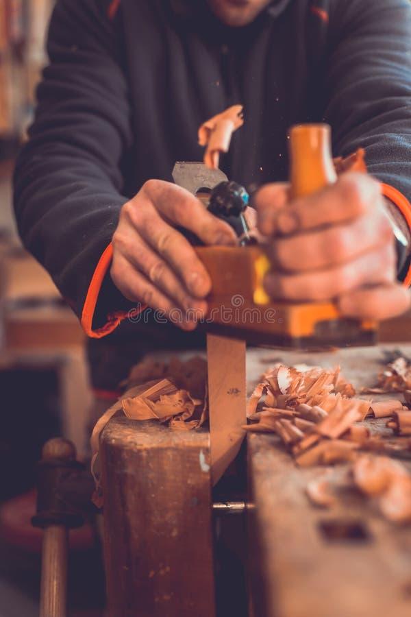 木匠与节理面木板条一起使用在车间,木匠与在木背景的飞机一起使用 库存照片