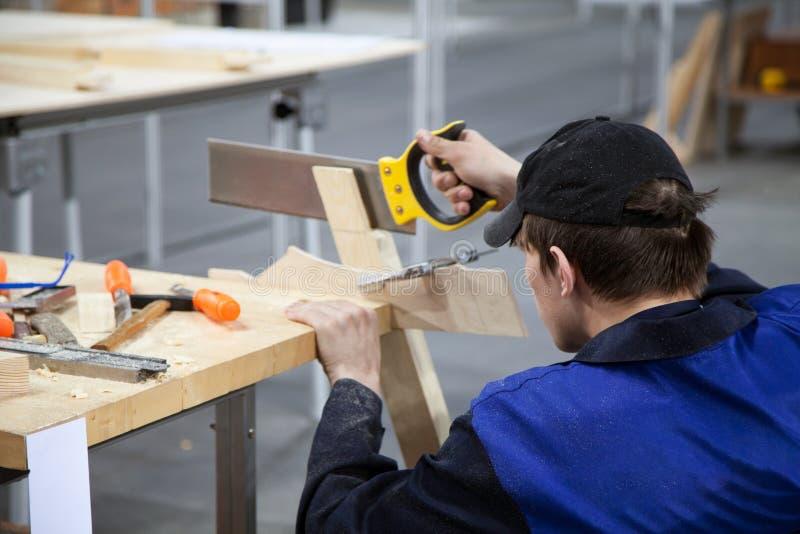 木匠与锯和木头一起使用在车间 免版税图库摄影