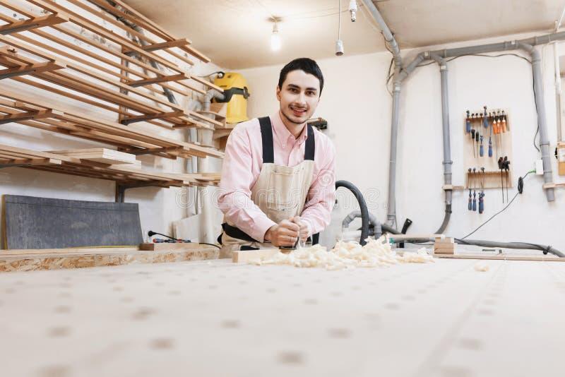 木匠与飞机和木板条一起使用在车间 库存照片