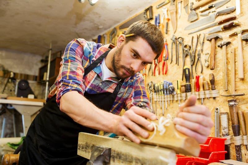 木匠与飞机和木头一起使用在车间 库存照片