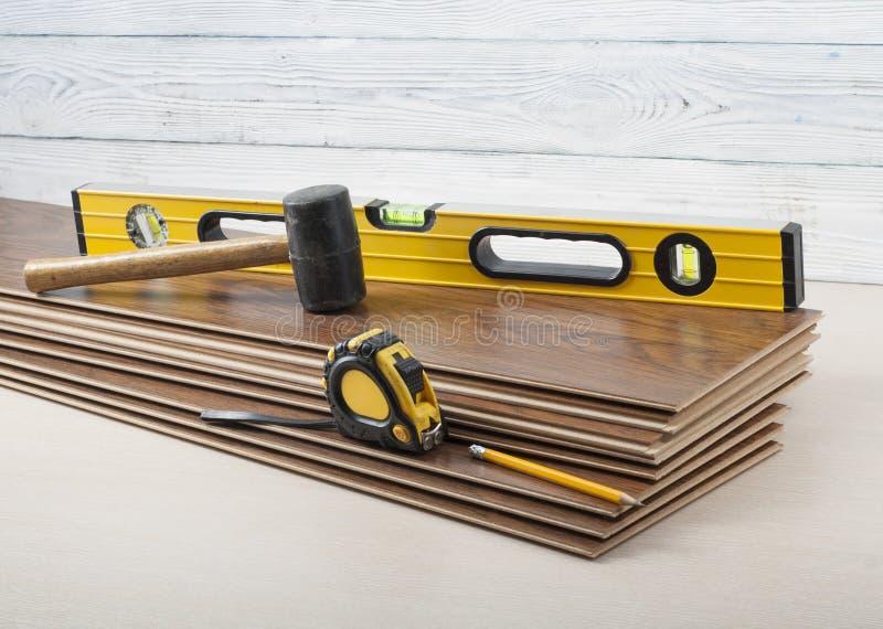 木匠业概念 不同的工具成水平,卷尺,在新的层压制品的地板的橡胶锤子 复制文本的空间 库存图片