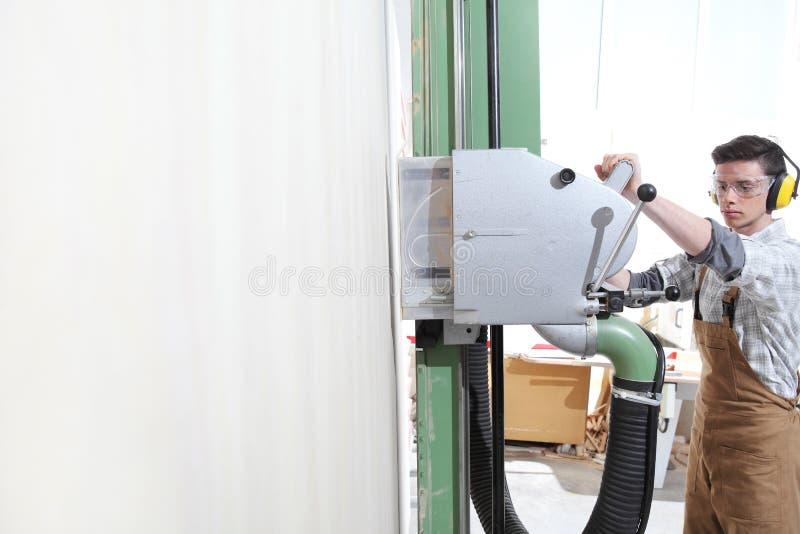 木匠人工作在木匠业里,切开了与垂直的圆锯机器的一个木盘区,保护与耳朵笨拙的人,玻璃 库存图片