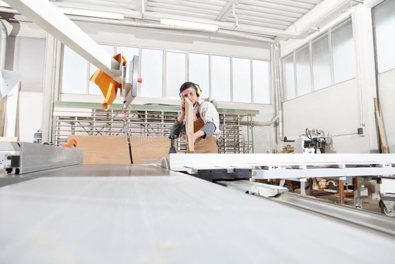 木匠人工作在木匠业里,削减了有圆锯机器的一个木板,保护与耳朵笨拙的人 图库摄影