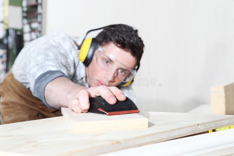 木匠人工作在木匠业里,有沙纸的铺沙的木板,保护与耳朵笨拙的人,玻璃 库存图片