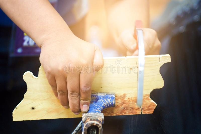 木匠使用一把锯切开木头 木匠,一个人,做了锯木头,背景给上釉与金银铜合金的纸 免版税图库摄影