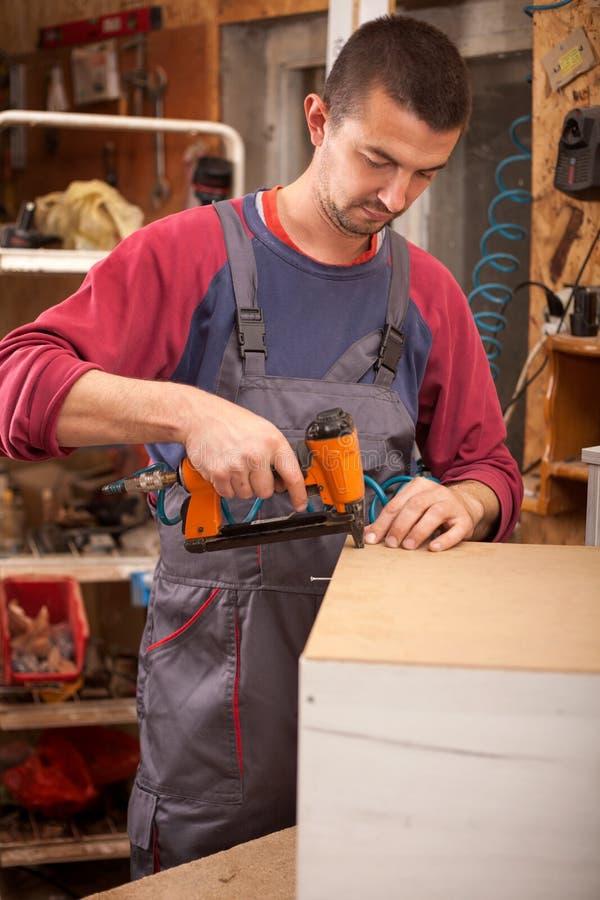木匠使用一杆专业订书机或钉子枪 免版税图库摄影