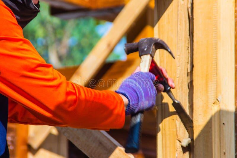 木匠使用凿子和锤子挖沟垂直线 在挖沟w期间,关闭木匠的手有凿子和锤子的 库存图片