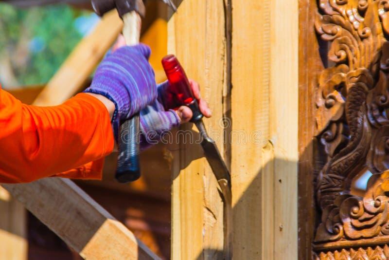 木匠使用凿子和锤子挖沟垂直线 在挖沟w期间,关闭木匠的手有凿子和锤子的 免版税库存照片