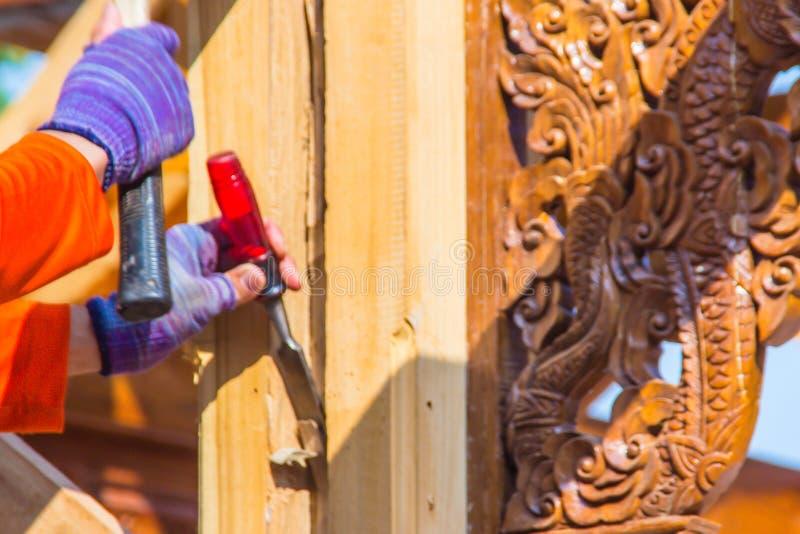 木匠使用凿子和锤子挖沟垂直线 在挖沟w期间,关闭木匠的手有凿子和锤子的 库存照片