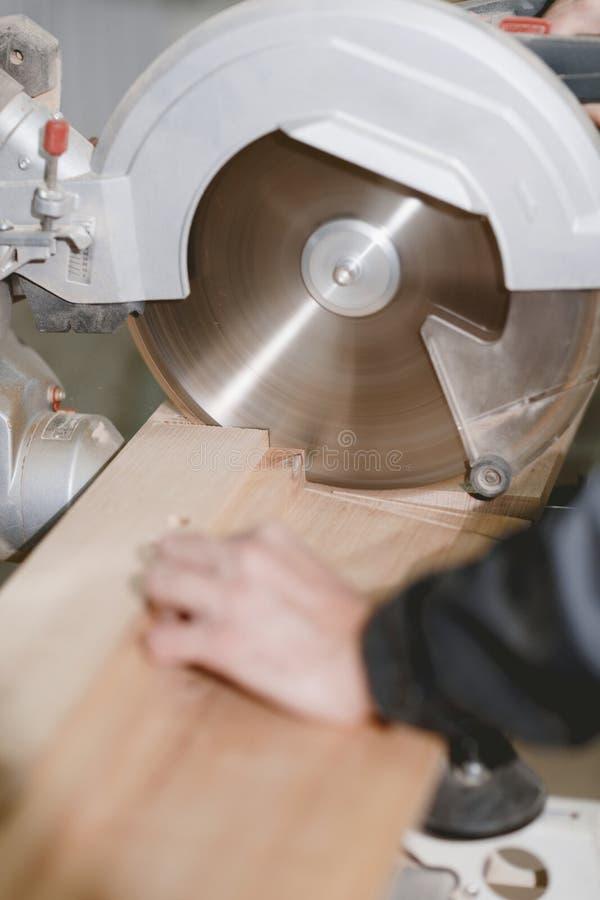 木匠切开木头酒吧在一台金属车床的有切开的木头一把锋利的圆的刀子的 特写镜头 图库摄影