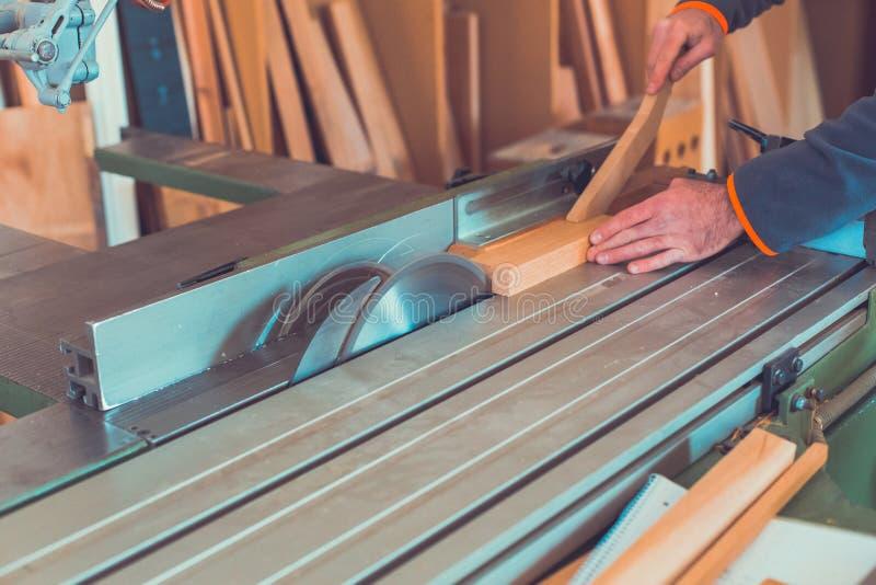 木匠参与处理木头在锯木厂 工作地点转台式一个板条平面人男性制造商行动尘土DIY人Pers 免版税库存图片