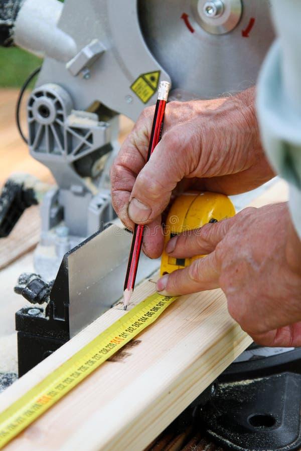 木匠在切开前采取关于一个木板的笔记 库存照片
