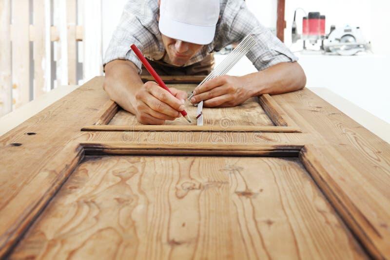 木匠在工作测量与米和铅笔在木头bac 图库摄影