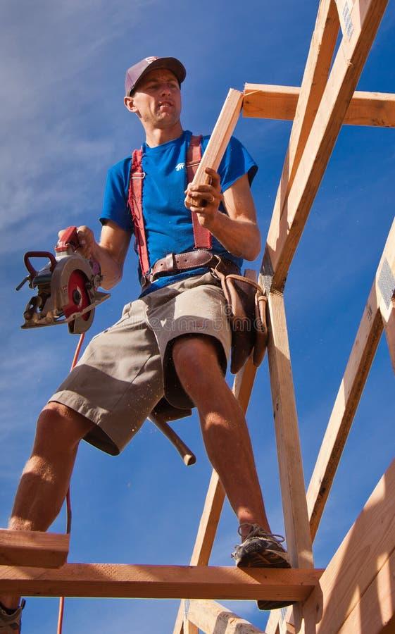 木匠在新的家大厦屋顶工作 免版税库存图片