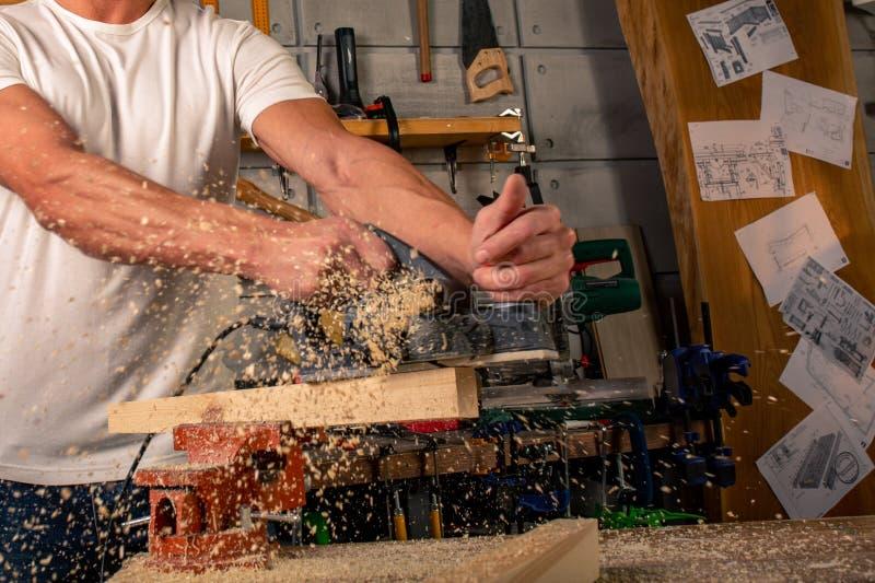 木匠在木材加工工作机械工具 锯与一把圆锯的家具细节 锯零件的过程 库存照片