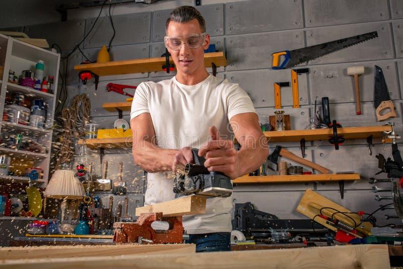 木匠在木材加工工作机械工具 锯与一把圆锯的家具细节 锯零件的过程 免版税图库摄影