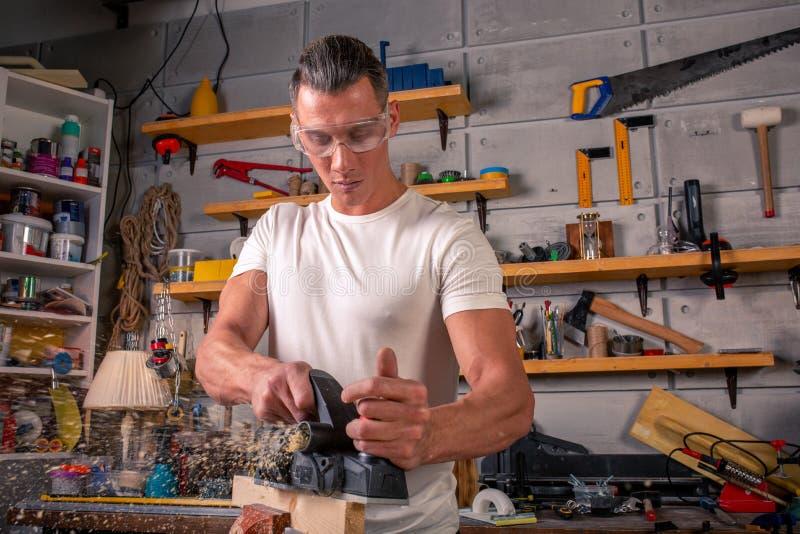 木匠在木材加工工作机械工具 锯与一把圆锯的家具细节 锯零件的过程 库存图片