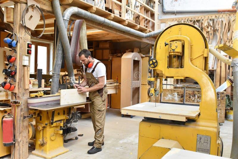 木匠在细木工技术-木材加工和sawi的车间里工作 免版税图库摄影