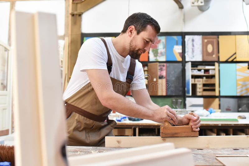 木匠在细木工技术-木材加工和sawi的车间里工作 图库摄影