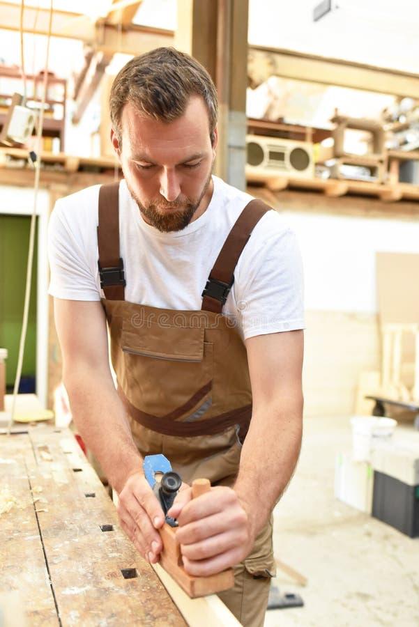 木匠在细木工技术-木材加工和sawi的车间里工作 库存照片