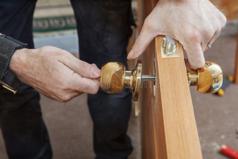 木匠在门叶子安装有锁的把柄 库存照片