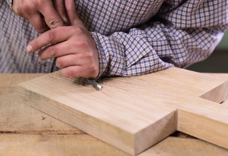 木匠实施日志概略的来回跟踪工作 削减与凿子的手橡木板 图库摄影