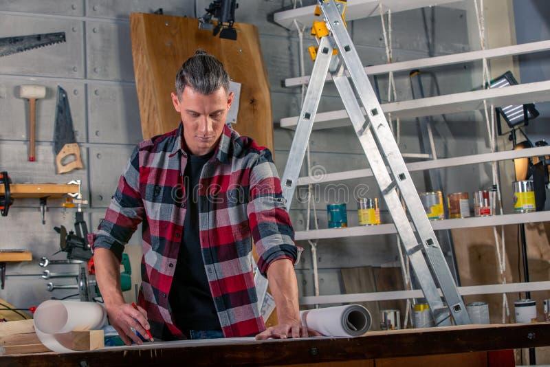 木匠工作 学习画的项目的木匠 以车间为背景 免版税库存图片