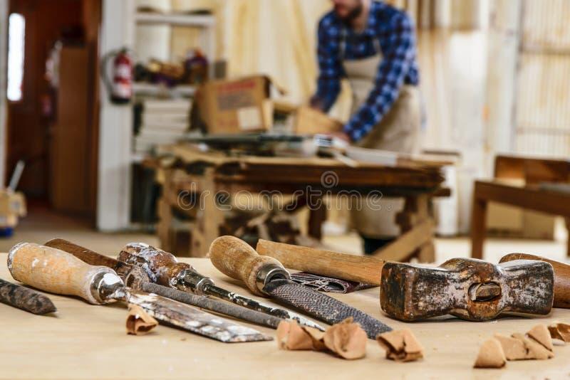 木匠工具 凿子或蛾眉凿木头的在工作在工作凳的木匠 木匠业车间 库存图片