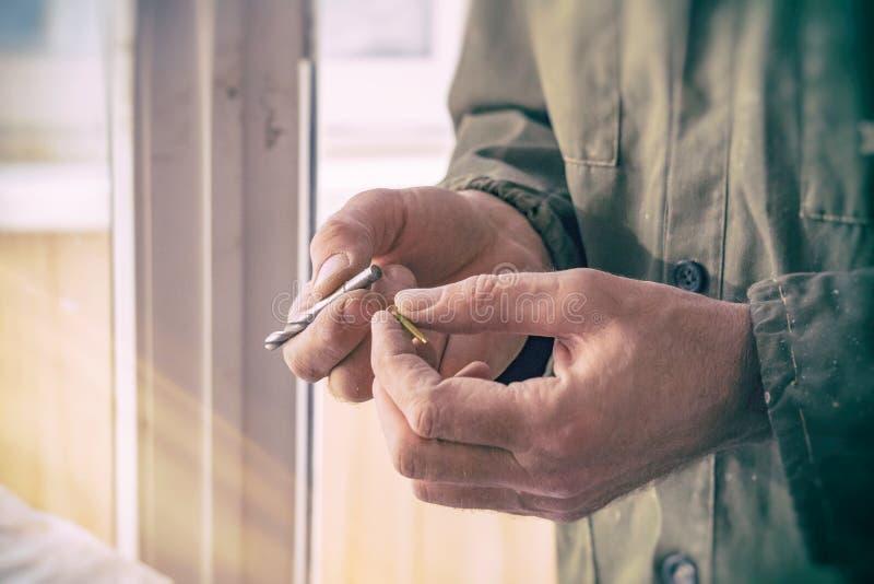 木匠拿着钻头和螺丝 免版税图库摄影