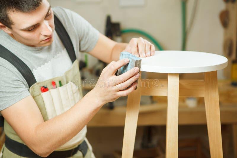 木匠波兰圆的椅子在车间 围裙的木工 库存照片