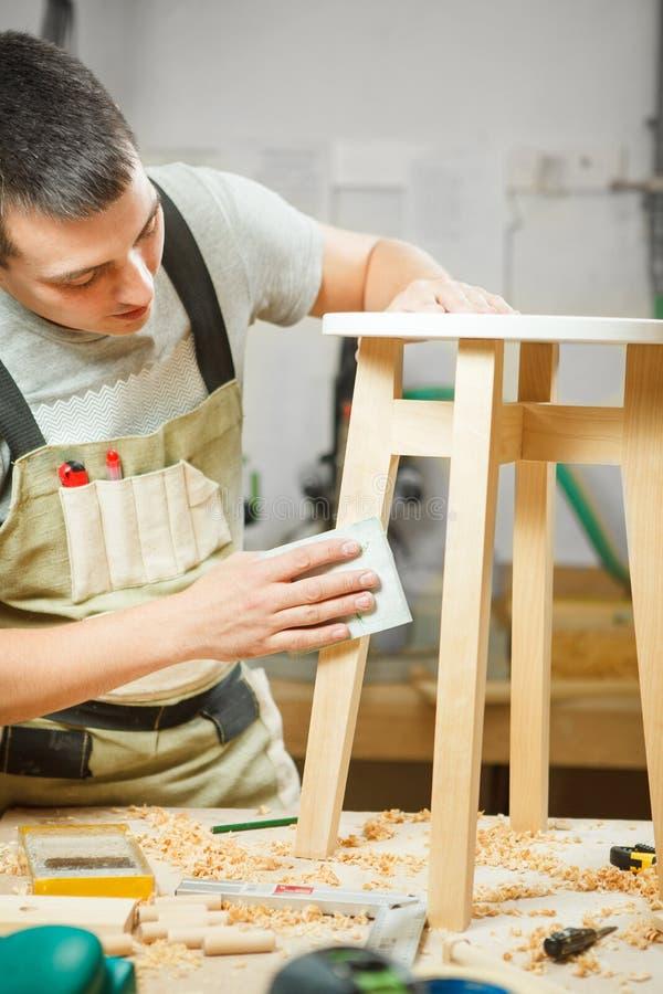 木匠波兰圆的椅子在车间 围裙的木工 免版税库存图片