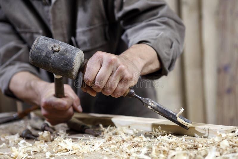 木匠的手有锤子和凿子的在工作凳在木匠业方面 库存照片