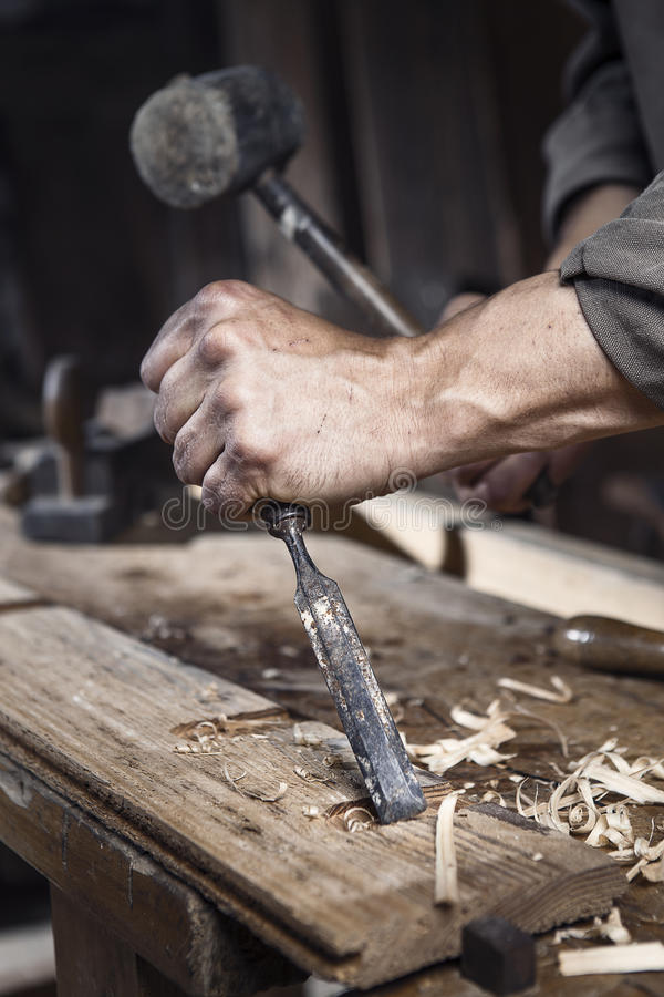 木匠的手有锤子和凿子的 库存图片